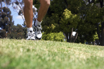 Man jogging on grass in park, low section, surface level, focus on trainers