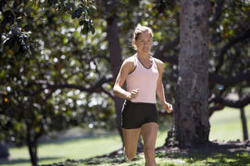 Woman jogging in park, trees in background