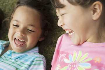 Two girls (3-5) lying on grass, laughing, close-up, overhead view