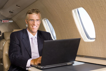 Businessman using laptop computer on aeroplane, smiling, portrait