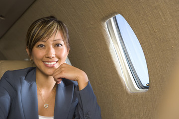Businesswoman on aeroplane, smiling, close-up