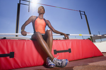 Female pole vault athlete, low angle view (lens flare)