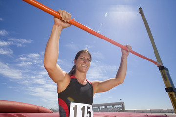 Young female athlete with hands on bar, low angle view (lens flare)