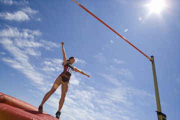 Young female athlete preparing to jump over bar, low angle view (lens flare)