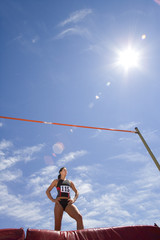 Young female athlete by bar, low angle view (lens flare)
