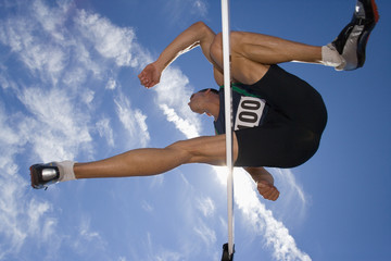 Male athlete jumping over hurdle, view from below