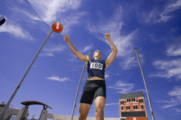 Male athlete throwing discus, low angle view