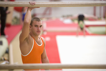 Male gymnast, hand on parallel bars, portrait