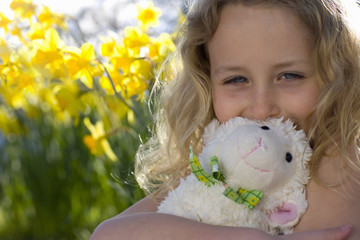 Girl hugging lamb toy in flowers