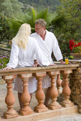 Couple in bathrobes standing at balcony railing