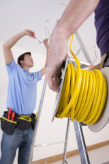 Close up of electrician holding cable spool with co-worker wiring ceiling in background