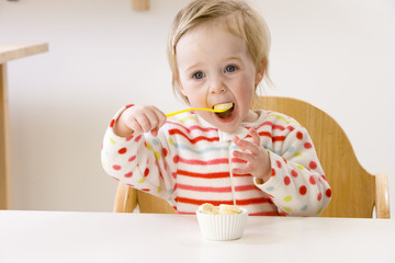 Baby girl in high chair eating banana slices