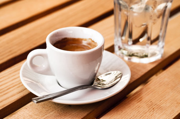 White espresso cup and glass of cold water