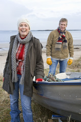 Couple standing by boat on beach
