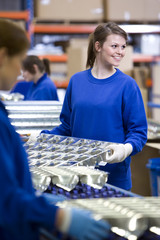Smiling worker moving aluminium light fittings in factory