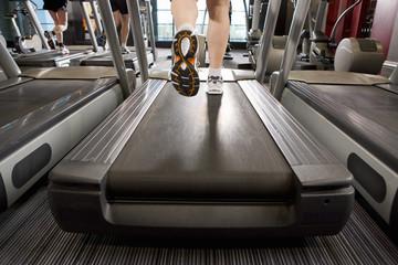 Legs of man running on treadmill in health club