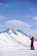 Skier taking photograph with digital camera on snowy mountain