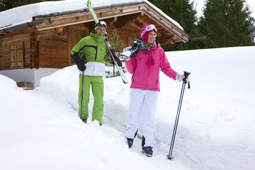 Couple standing in snow near lodge with skis