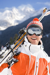 Smiling skier in goggles standing with skis