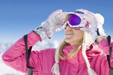 Smiling skier adjusting goggles