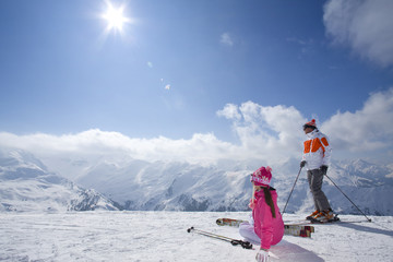 Photo sur Toile Gris Skiers sitting in snow looking at mountains