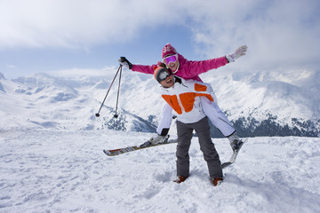 Skier giving girlfriend piggyback ride on mountain top