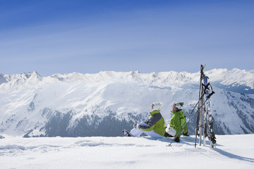 Couple sitting in snow on mountain top with skis