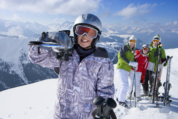 Family standing in snow on mountain top with skis