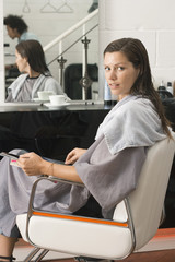 Woman sitting in hair salon, magazine in lap, side view, portrait, reflection in mirror