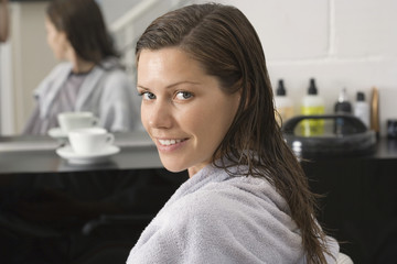 Woman sitting in hair salon, side view, smiling, portrait, reflection in mirror