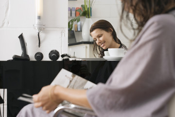 Woman sitting in hair salon, magazine in lap, side view, smiling, portrait, reflection in mirror