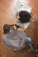 Young male hairdresser cutting woman's hair in salon, overhead view