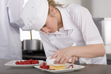 Trainee chef wiping plate of gourmet dessert in commercial kitchen