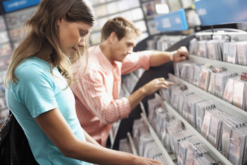 Young couple sifting through CDs in record shop, side view (tilt)