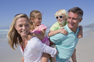 Parents piggybacking children on sunny beach