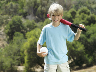 Blonde boy (7-9) standing in park with softball bat and ball, smiling, front view, portrait
