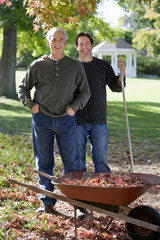 Senior man and adult son collecting autumn leaves in wheelbarrow in garden, smiling, portrait