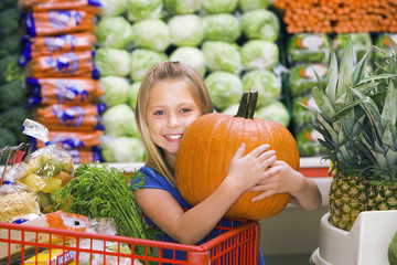 Girl (7-9) standing in vegetable section of supermarket, clutching large pumpkin, smiling, portrait