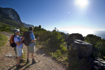 Mature couple hiking on mountain trail, looking at Atlantic Ocean horizon in bright sunlight, side view (lens flare)
