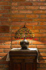 lamp of stained-glass on red brick wall