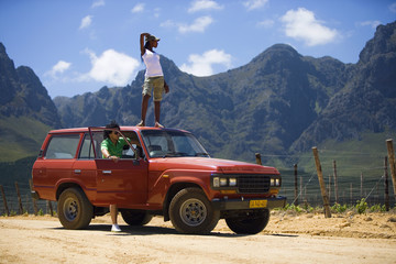 Young couple standing beside parked red SUV on dirt track in mountain valley, woman on roof, looking at scenery