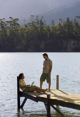 Two young men talking on lake jetty, man leaning against wooden post, using laptop, profile