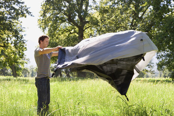 Man assembling tent on camping trip in woodland clearing, side view