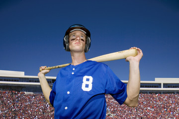 Baseball player, in number '8' blue uniform, helmet and face paint, standing on pitch with bat behind head, low angle view, portrait