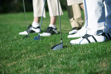 Two mature couples standing on golf course, focus on golf shoes, clubs and grass, side view, low section (surface level)