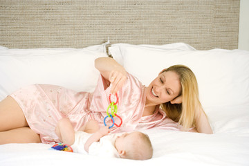Mother and baby girl (9-12 months) lying on bed, mother holding toys, smiling