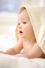 Baby girl (9-12 months) wearing towel on head, close-up