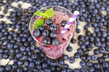 Blueberry smoothie in a glass jar with a straw and sprig of mint