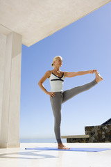 Mature woman in standing yoga position on exercise mat outdoors, low angle view