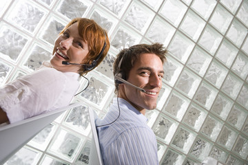 Businessman and woman wearing headsets sitting back to back by glass block wall, smiling, portrait (tilt)
